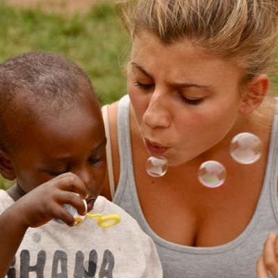 Una voluntaria social soplando burbujas con un niño ghanés.